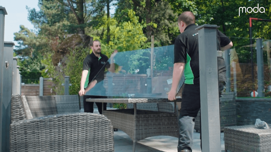 moda installers lifting glass top onto outdoor dining table